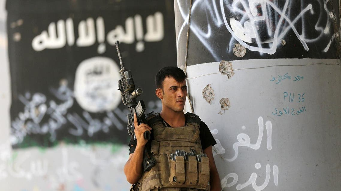 a member of Iraqi counterterrorism forces stands guard near Islamic State militant graffiti in Fallujah, Iraq. AP