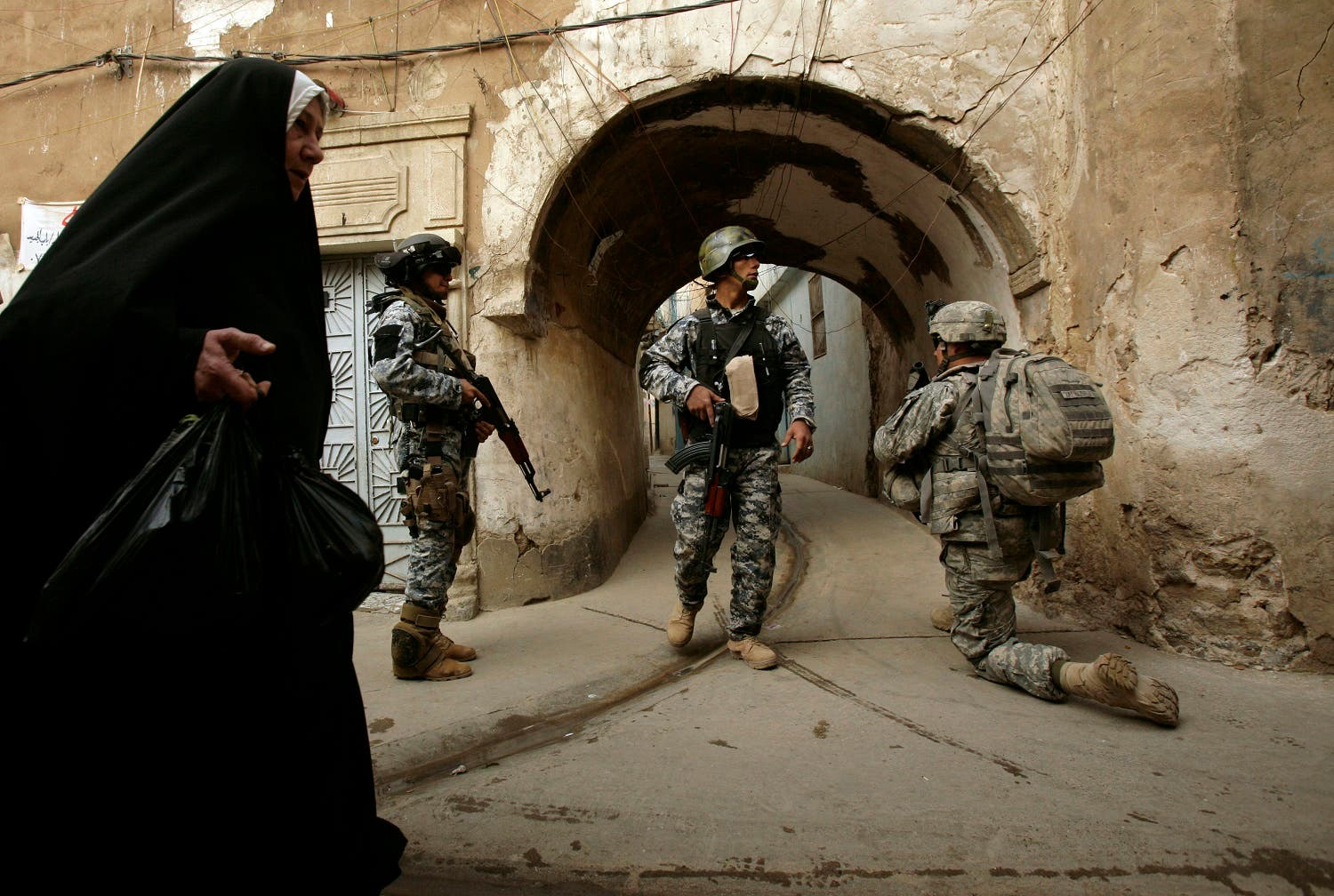 an Iraqi woman passes U.S. troops AP