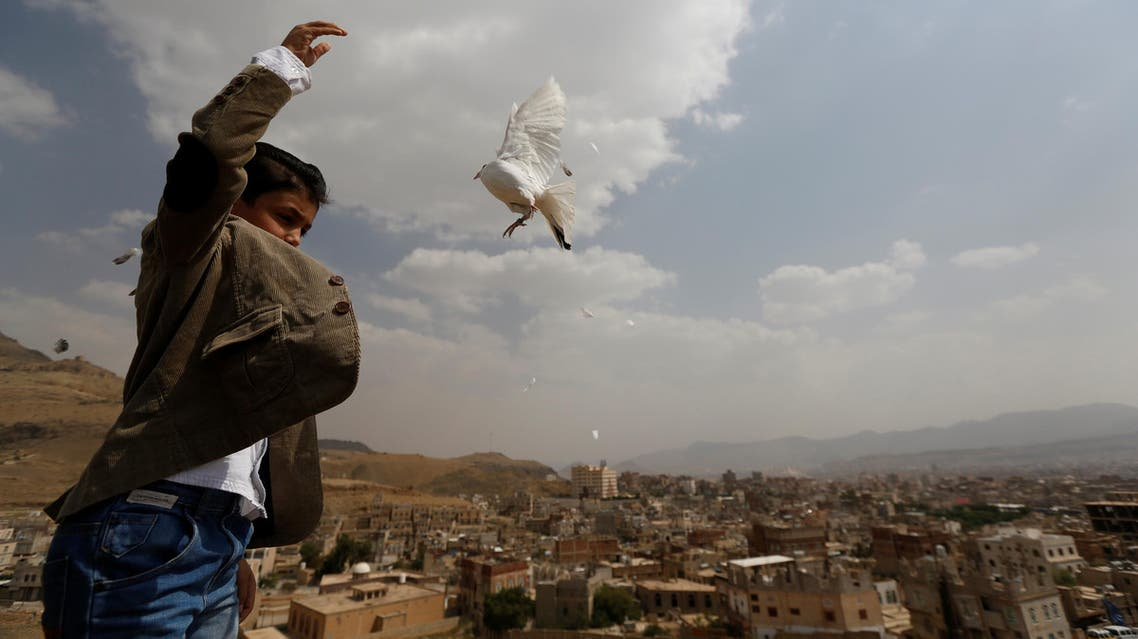 A boy releases a dove as part of a campaign to push Yemeni negotiators to in Kuwait to reach a peace agreement, in Sanaa, Yemen June 29, 2016. REUTERS/
