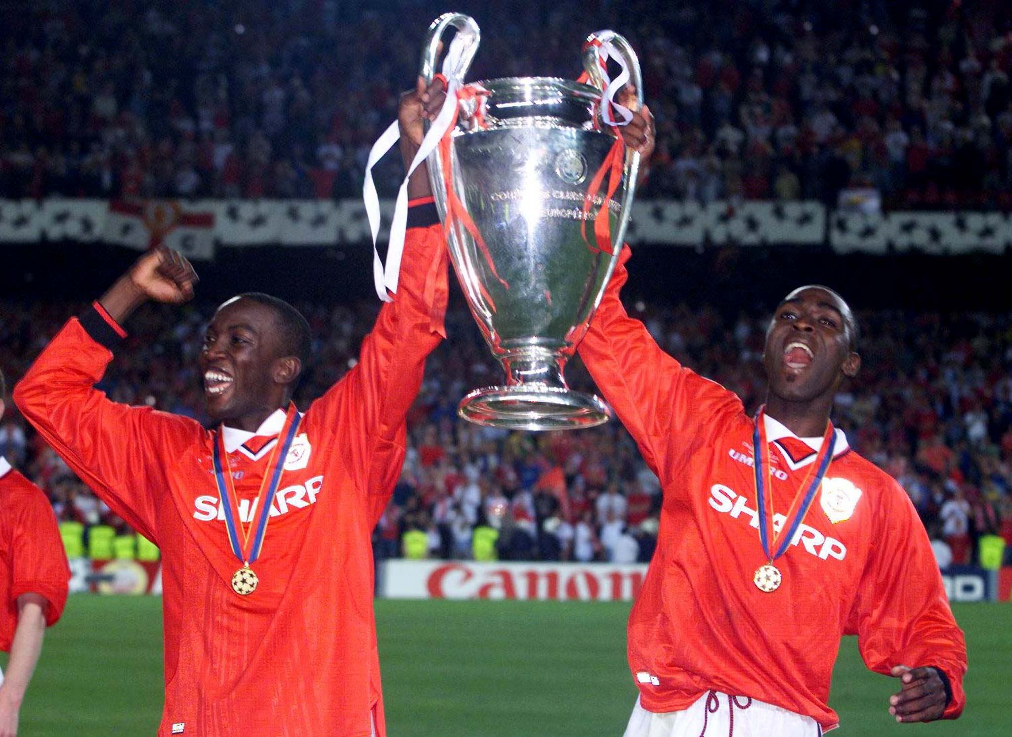 Manchester United's Dwight Yorke (L) and Andy Cole hold the cup as they celebrate their victory over Bayern Munich in the European Cup final at Barcelona's Nou Camp stadium May 26. Manchester United won the match 2-1. (Reuters)