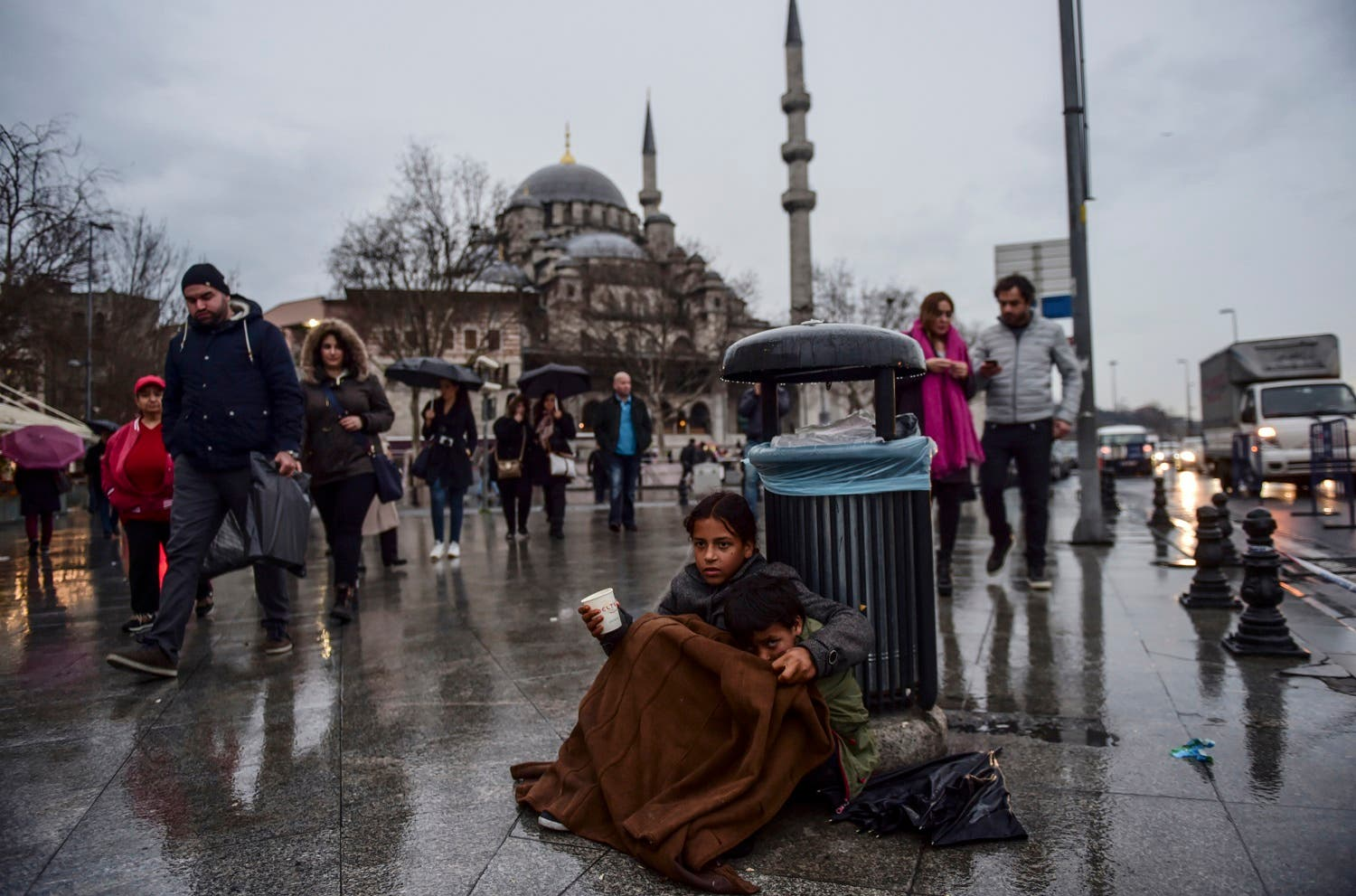 A Syrian girl begs in the street of Istanbul as she hugs another child. (AFP)
