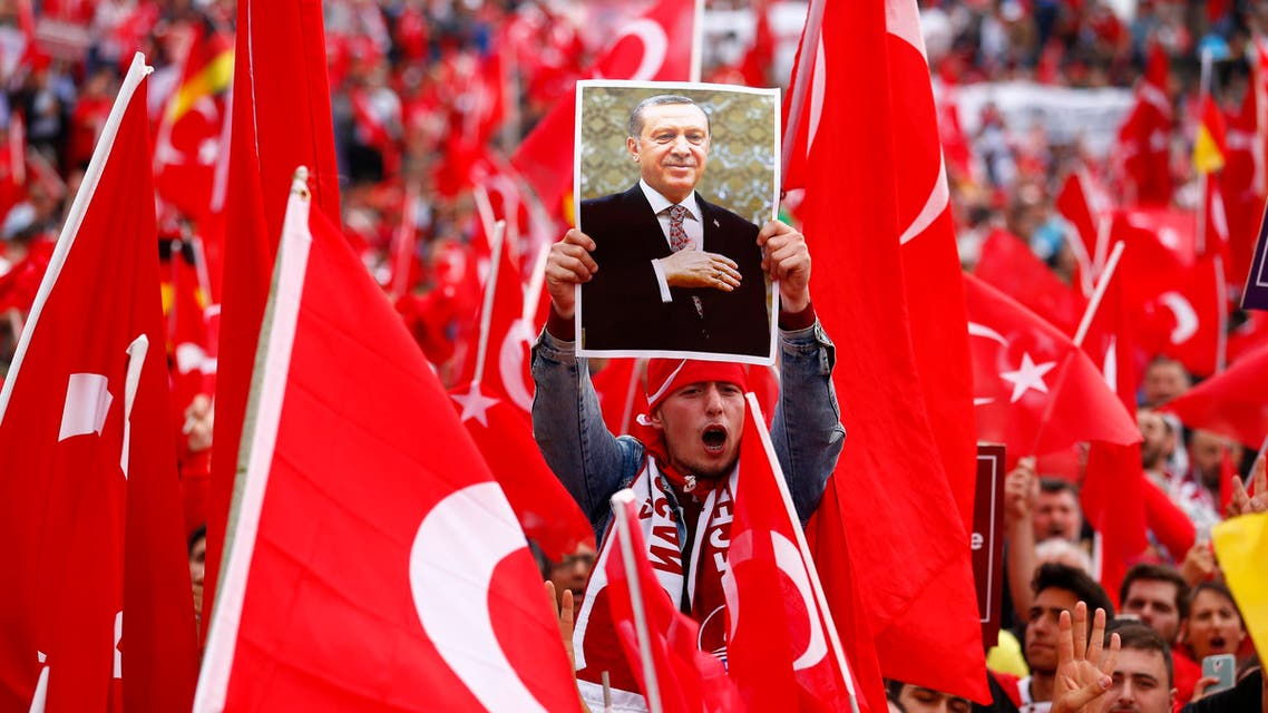 A supporter of Turkish President Tayyip Erdogan holds up a picture during a pro-government protest in Cologne, Germany July 31, 2016. REUTERS