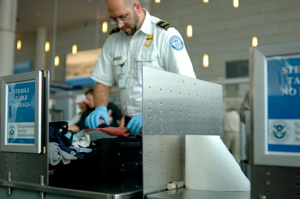 A TSA agent searches luggage at an airport. (Shutterstock)