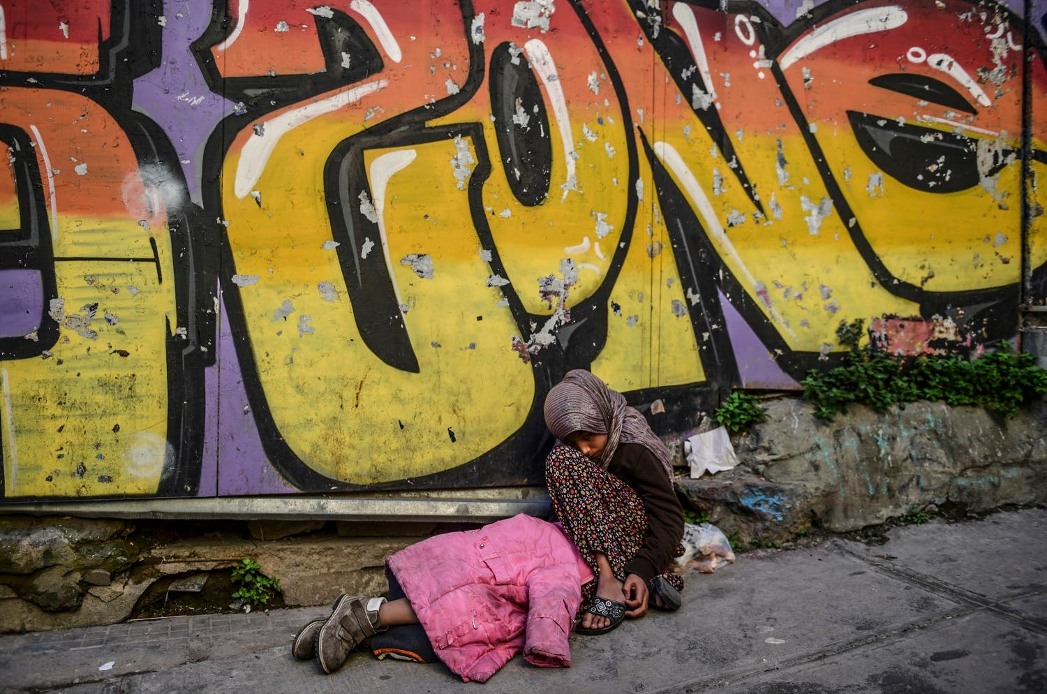 A Syrian girl begs in the street as another child sleeps next to her, in downtown Istanbul. (AFP)