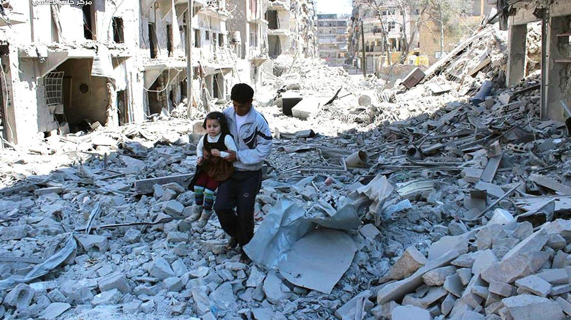 In This April 21, 2014 photo, provided by the anti-government activist group Aleppo Media Center (AMC), a Syrian man holding a girl as he stands on the rubble of houses that were destroyed by Syrian government forces air strikes in Aleppo. (AP)