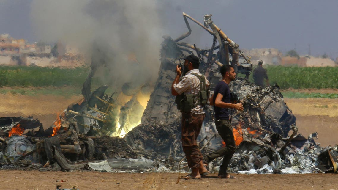 Men inspect the wreckage of a Russian helicopter that had been shot down in the north of Syria's rebel-held Idlib province, Syria August 1, 2016. REUTERS