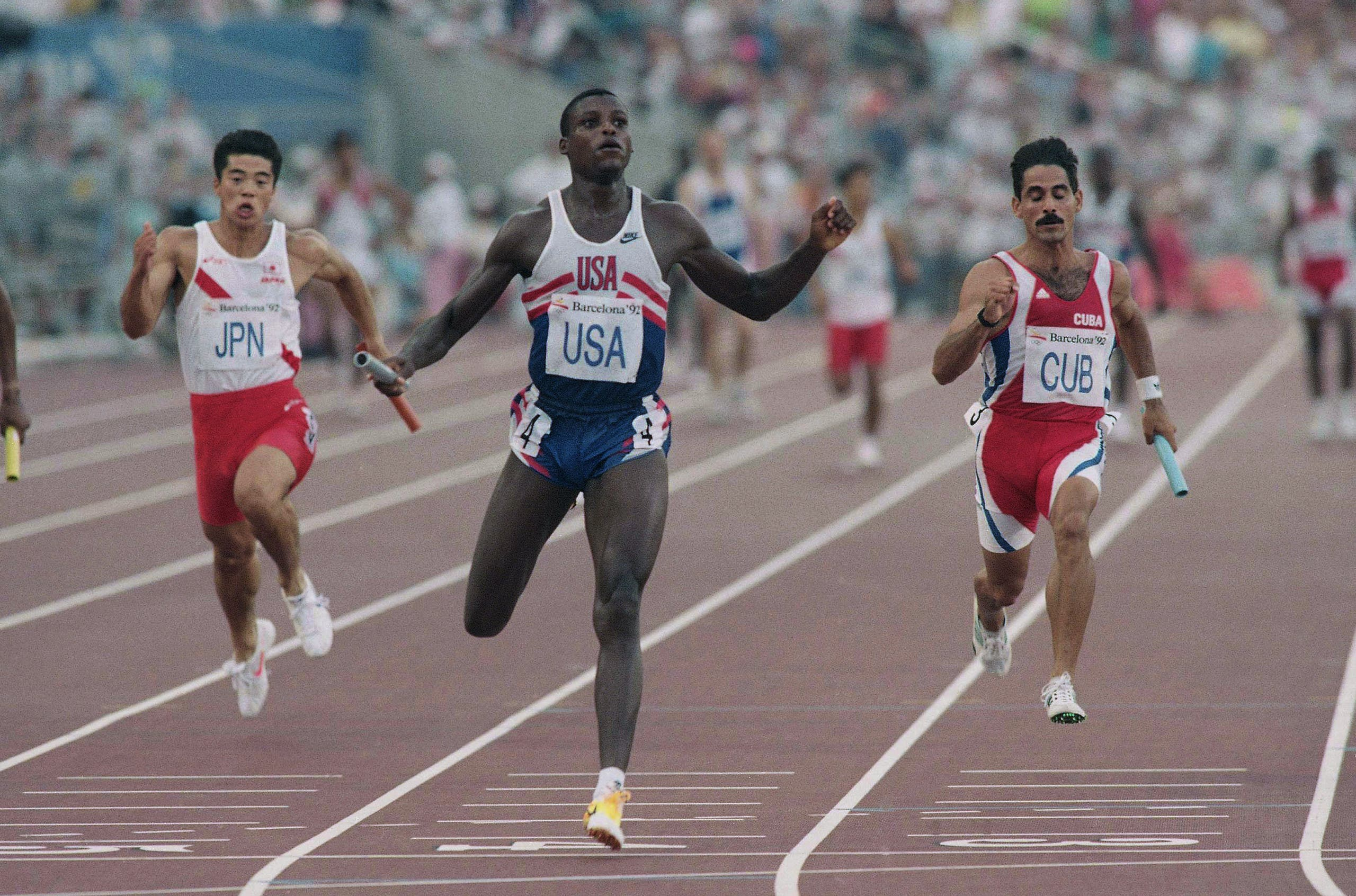 The USA's Carl Lewis, center, Houston, Tex., hits the line ahead of Japan's Tatsuo Sugimoto (left), and Cuba's Jorge Luis Aguilera Ruiz, in the semi-final of the Men's 4×100 meter relay at Barcelona's Olympic Stadium, Friday, August 7, 1992. Each team qualified for the final with Lewis finishing first, Ruiz second and Sugimoto fourth. (AP)