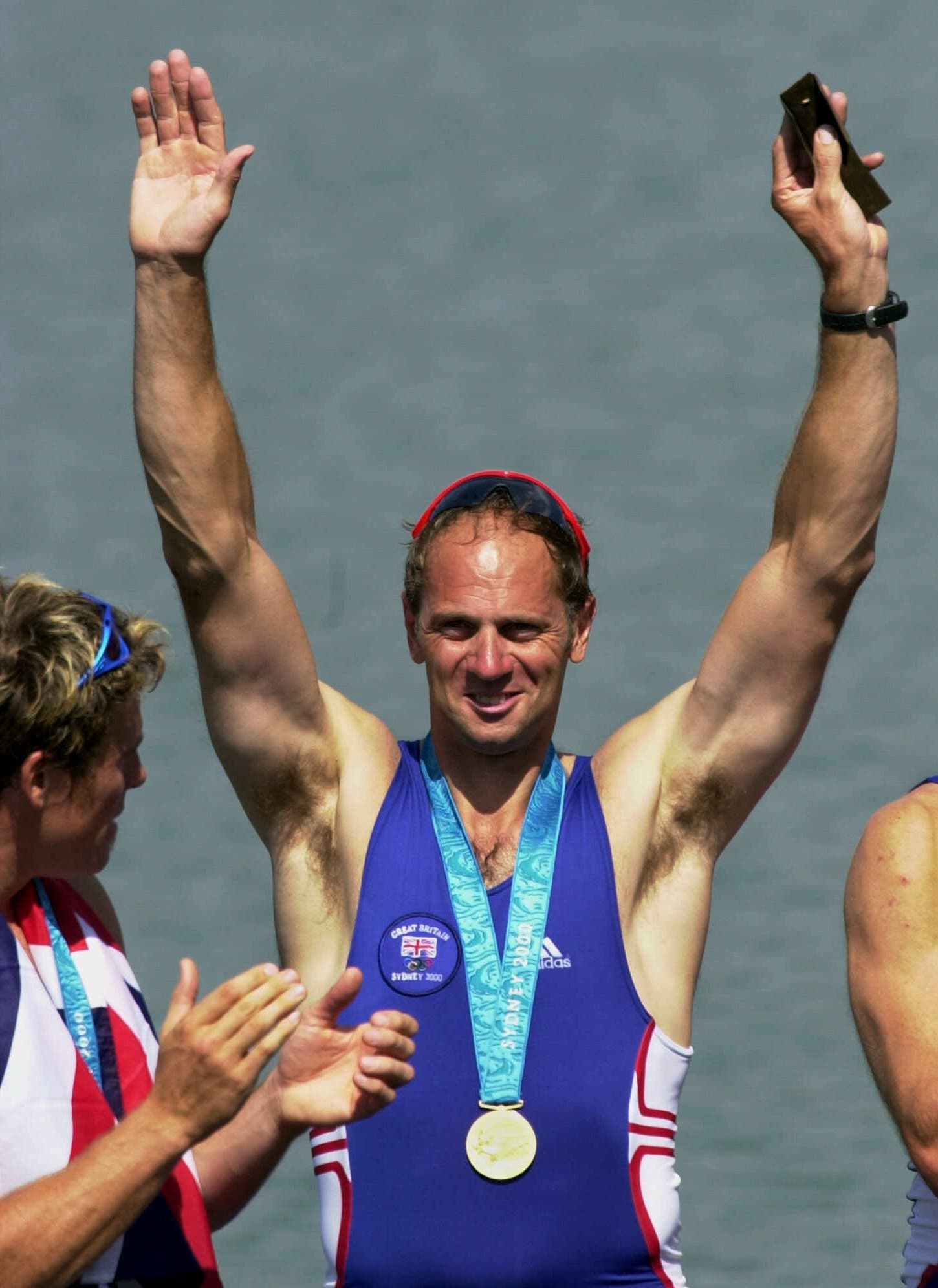 Steven Redgrave acknowledges the crowd after receiving a special gold pin Saturday, Sept. 23, 2000, at the Sydney International Regatta Center in Penrith, Australia. He received the pin in honor of winning five consecutive gold medals. Looking on at left is teammate James Cracknell. (AP)