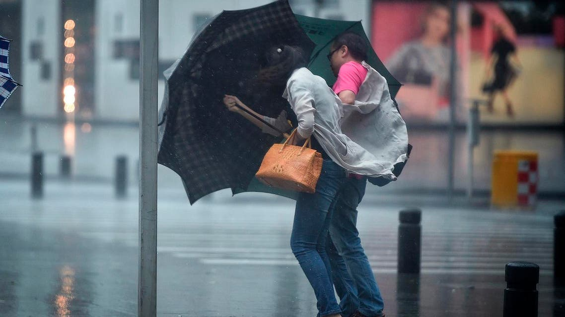 People carrying umbrellas brave the strong winds (Photo: AP)