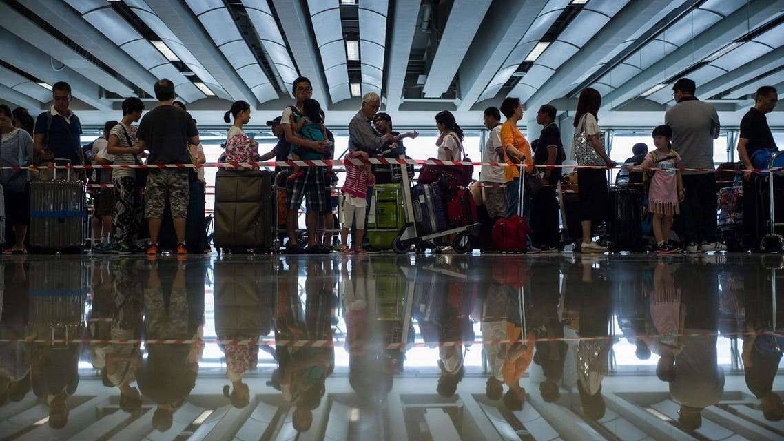 Passengers queue as they wait to find out the status of their flights after Typhoon Nida caused chaos at Hong Kong's international airport (Photo: AFP)