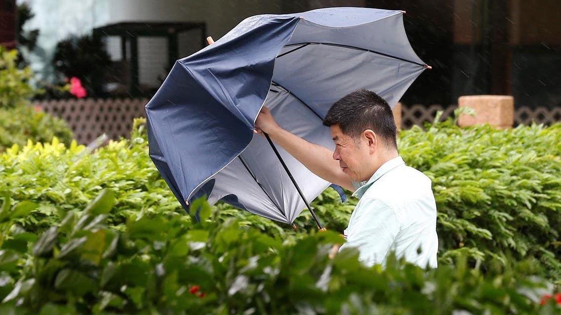 A man with an umbrella struggles against the heavy winds (Photo: Reuters)