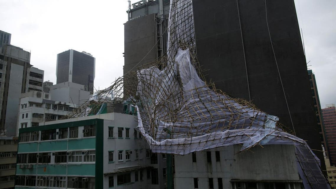 Collapsed bamboo scaffolding brought down by Typhoon Nida is seen hanging from the side of a building in Wanchai district in Hong Kong (Photo: Reuters)