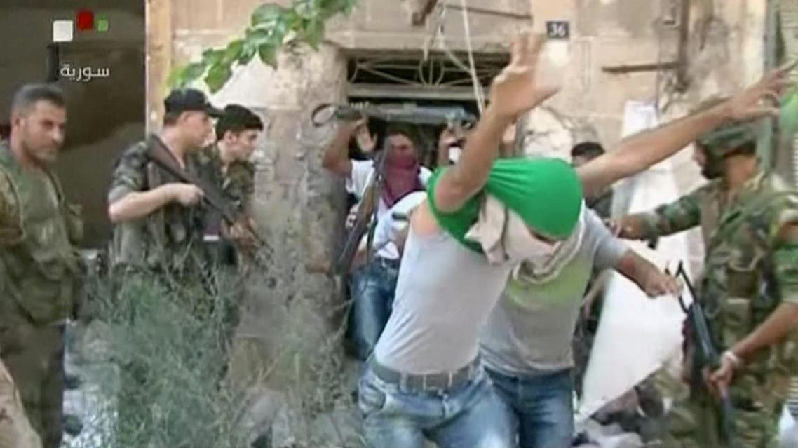 This still image from Syrian state TV video, shows young men with their faces covered surrendering to government forces, in Aleppo, Syria, Saturday, July 30, 2016, Syrian state media is reporting that dozens of families have started leaving besieged rebel-held neighborhoods in the northern city of Aleppo after the government opened safe corridors for civilians and fighters who want to leave. The Russian military says 169 civilians have left through the corridors since they were set up, but Syrian opposition activists say no civilians have left besieged parts of the city. (Syrian State TV, via AP)