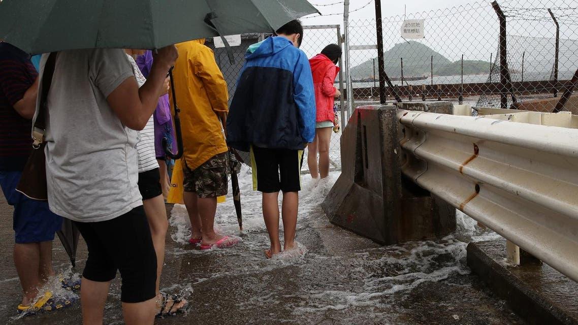 People play in the overflowing water caused by Typhoon Nida (Photo: AP)
