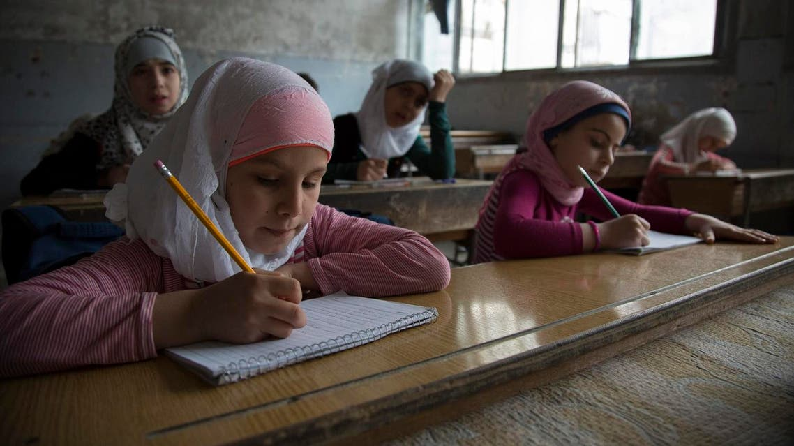 Syrian children attend a class at a primary school in Aleppo's rebel-held eastern district of Shaar on May 7, 2016. Displaced families returned home and schools reopened in rebel-held districts of Aleppo after a truce was extended for 72 hours in the battleground northern city. KARAM AL-MASRI / AFP