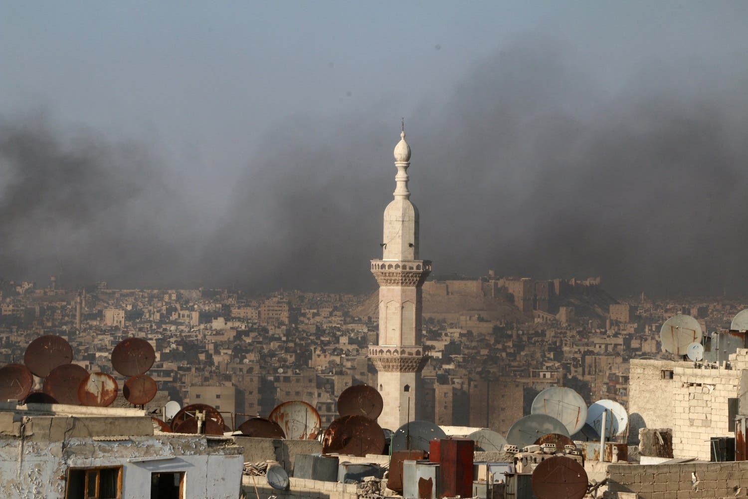 Smoke from burning tyres rises near a minaret of a mosque, which activists said are used to create smoke cover from warplanes, in Aleppo. (Reuters)