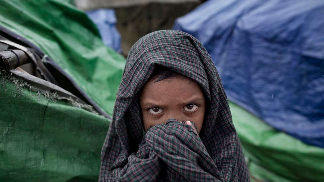 In this June 26 2014 photo, a Rohingya child covers his head and face with a cloth as he stands in the foreground of makeshift tents at Dar Paing refugee camp in north of Sittwe, Rakhine state, Myanmar. Boys and girls run around naked and barefoot on the muddy, narrow pathways, or play in dirty pools of sludge, exposing themselves to diarrhea, fever and waterborne diseases. (AP Photo/Gemunu Amarasinghe)