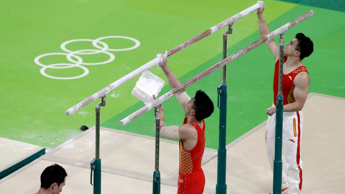 Members of the Chinese gymnastics team prepare the parallel bars before a training session (Photo: AP)