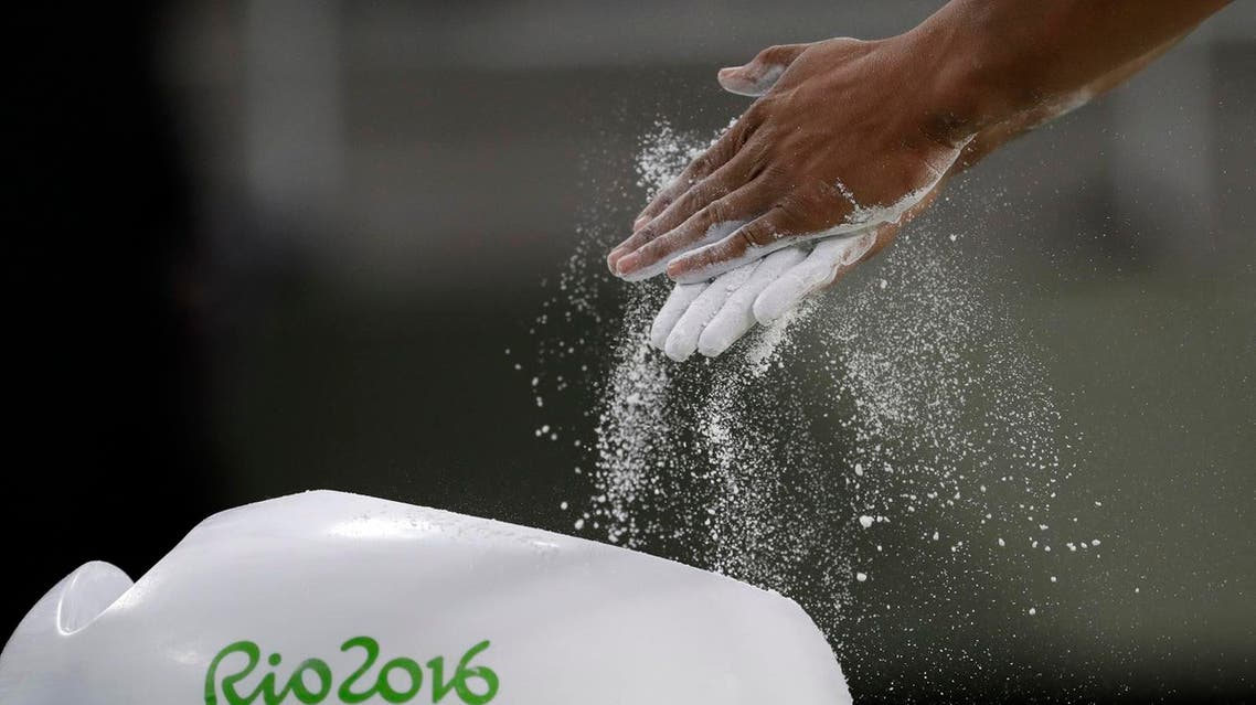 Gymnast Marios Georgiou from Cyprus rubs chalk on his hands before training (Photo: AP)