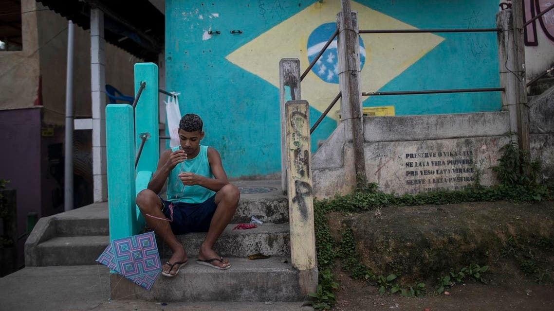 But for some life goes on like for this boy pictured prepares his kite before flying it at the Babilonia slum in Rio de Janeiro, Brazil (Photo: AP)
