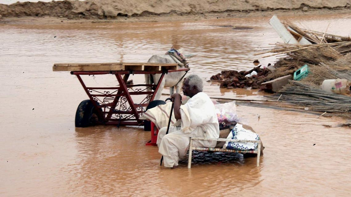 A Sudanese sits amongst the remains of his home following floods in Kassala, near Khartoum, Sudan.(AP)