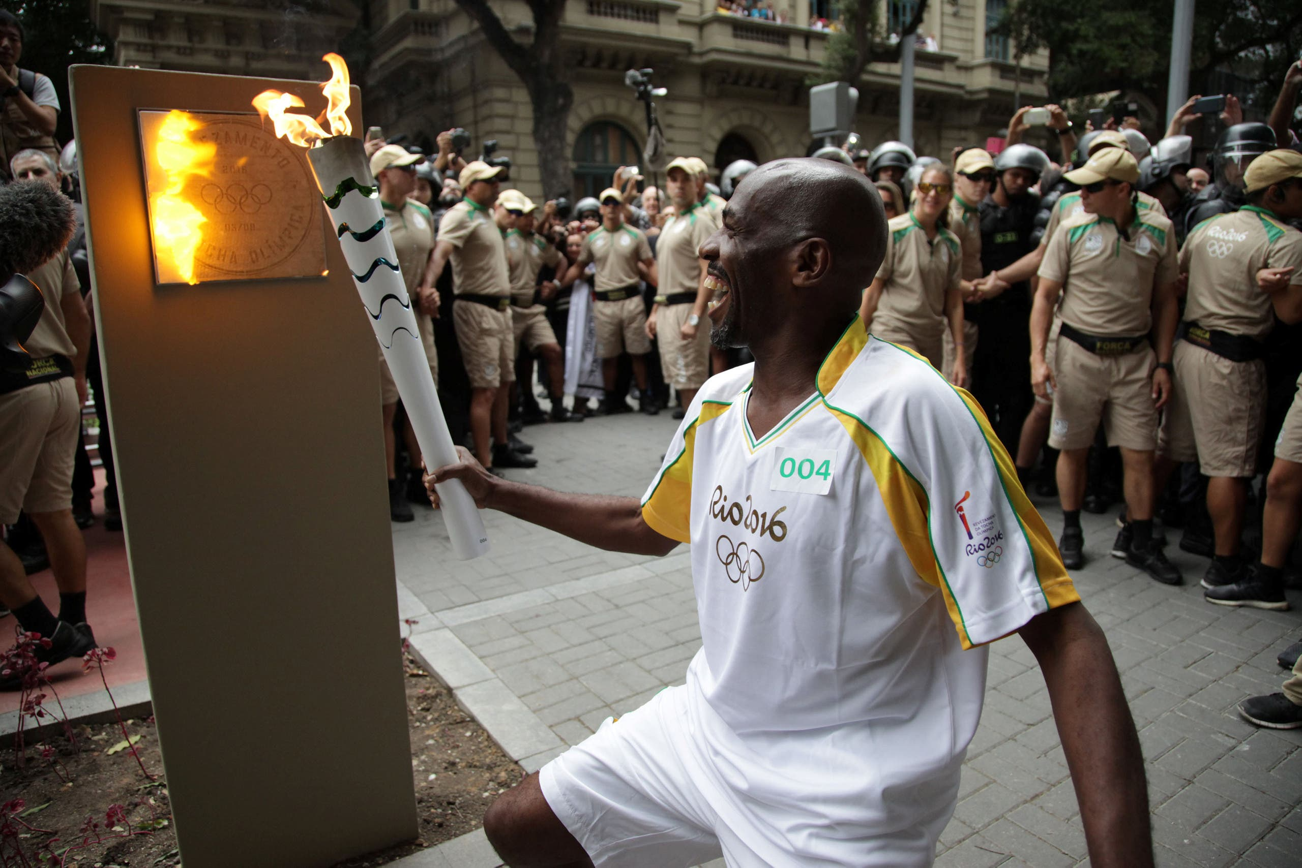 Street sweeper Renato Sorriso smiles while lighting the first of five posts with the Olympic torch in Rio de Janeiro. (Reuters)