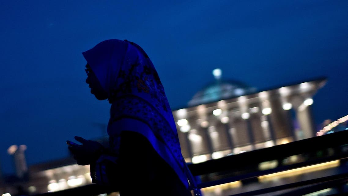 A Malaysian girls walks along the waterfront during sunset against the backdrop of the Iron Mosque in Putrajaya on May 10, 2015. AFP