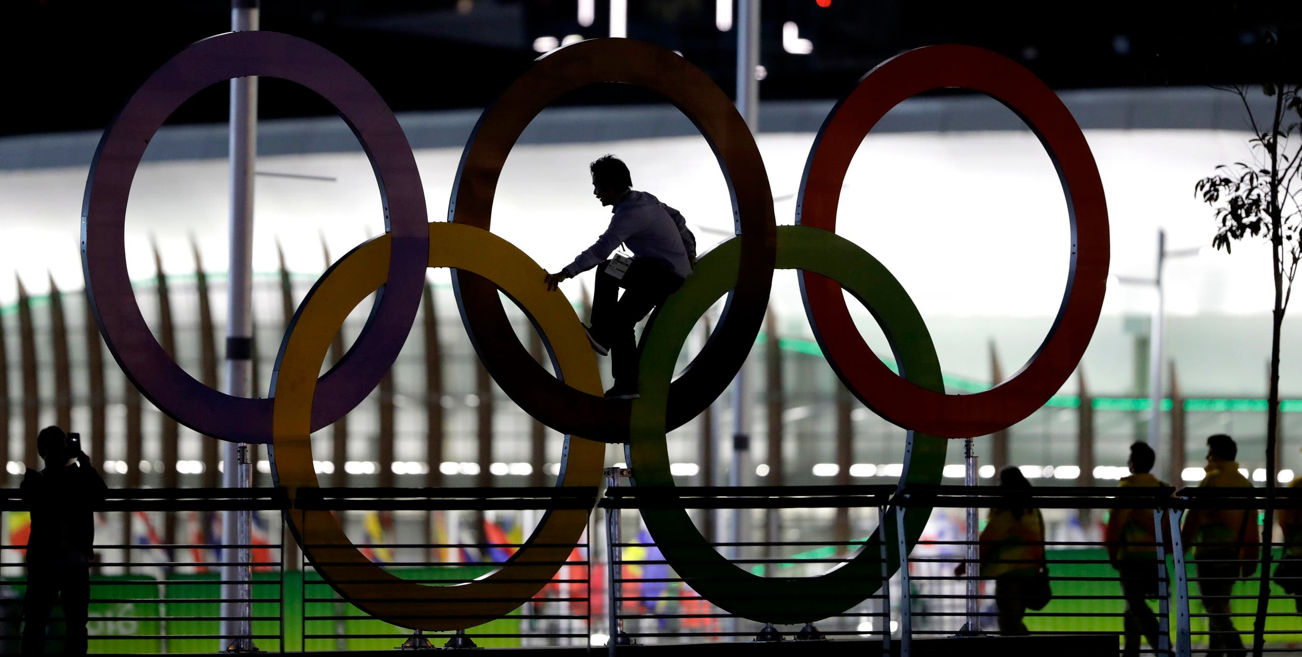 A man climbs on the Olympic rings near the basketball venue in the Olympic park on th eve before the opening ceremony of the 2016 Summer Olympics in Rio de Janeiro, Brazil, Thursday, Aug. 4, 2016. (AP)