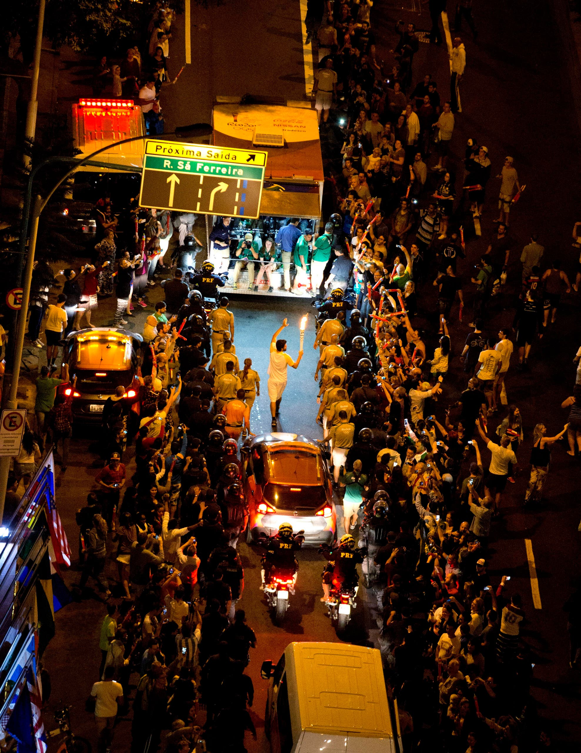 The Olympic torch is carried through the streets of Copacabana as the torch relay continues on its journey to the opening ceremony of the 2016 Summer Olympics in Rio de Janeiro, Brazil, early Friday, Aug. 5, 2016. (AP)