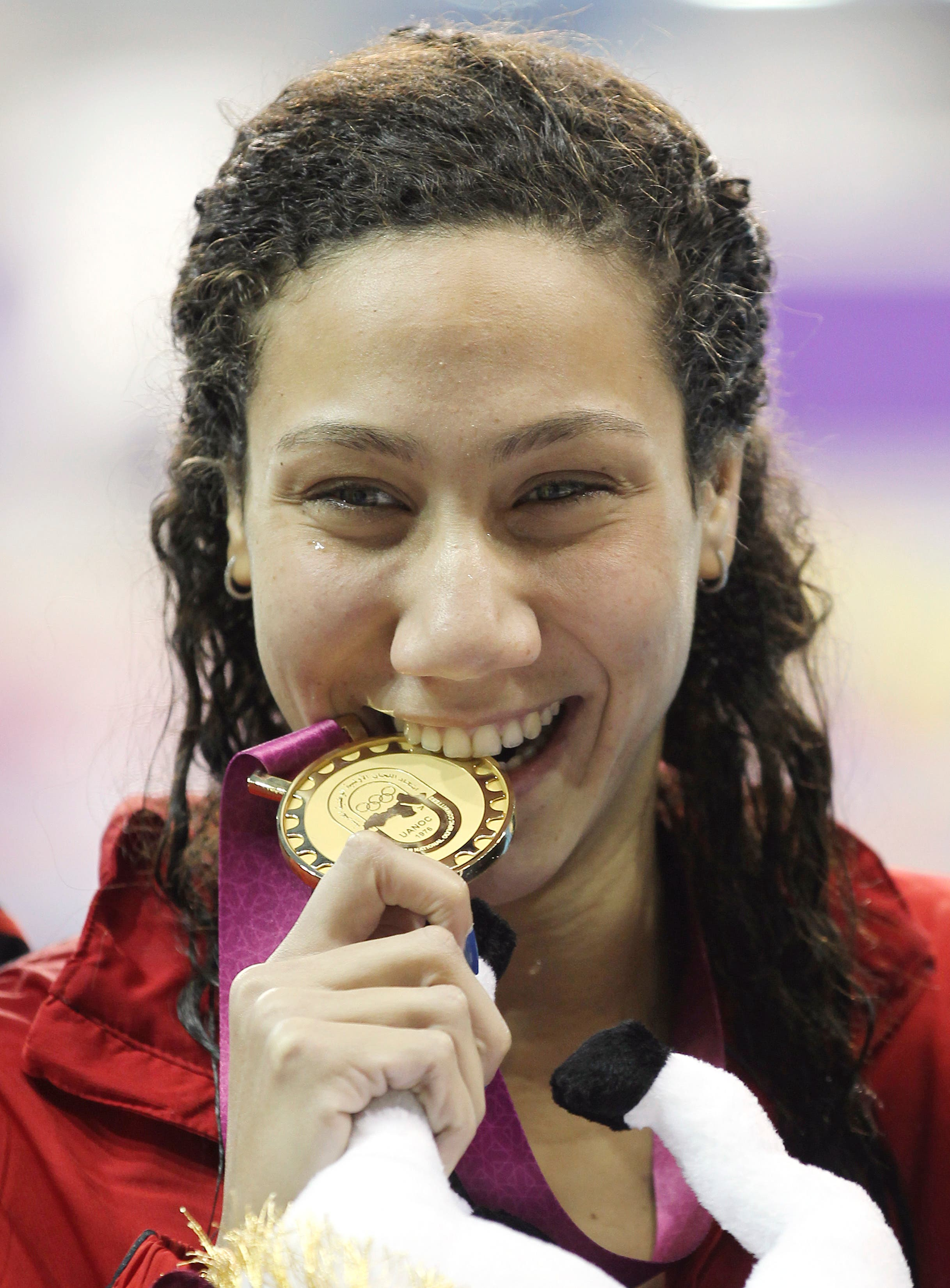 Farida Osman of Egypt celebrates after winning the gold medal at the Women's 100m Freestyle final at the Arab Games in Doha December 21, 2011. (Reuters)