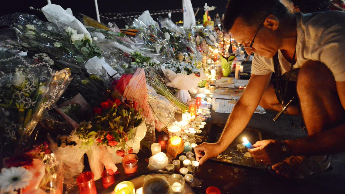 A man places candles near flowers that were left in tribute at makeshift memorials to the victims of the truck attack along the Promenade des Anglais in Nice, France, July 18, 2016. The University of California is re-evaluating its study abroad programs in the wake of the deaths of two UC Berkeley students in two weeks in separate terrorist attacks overseas that have raised questions about safety of international education trips, Reuters has learned. REUTERS