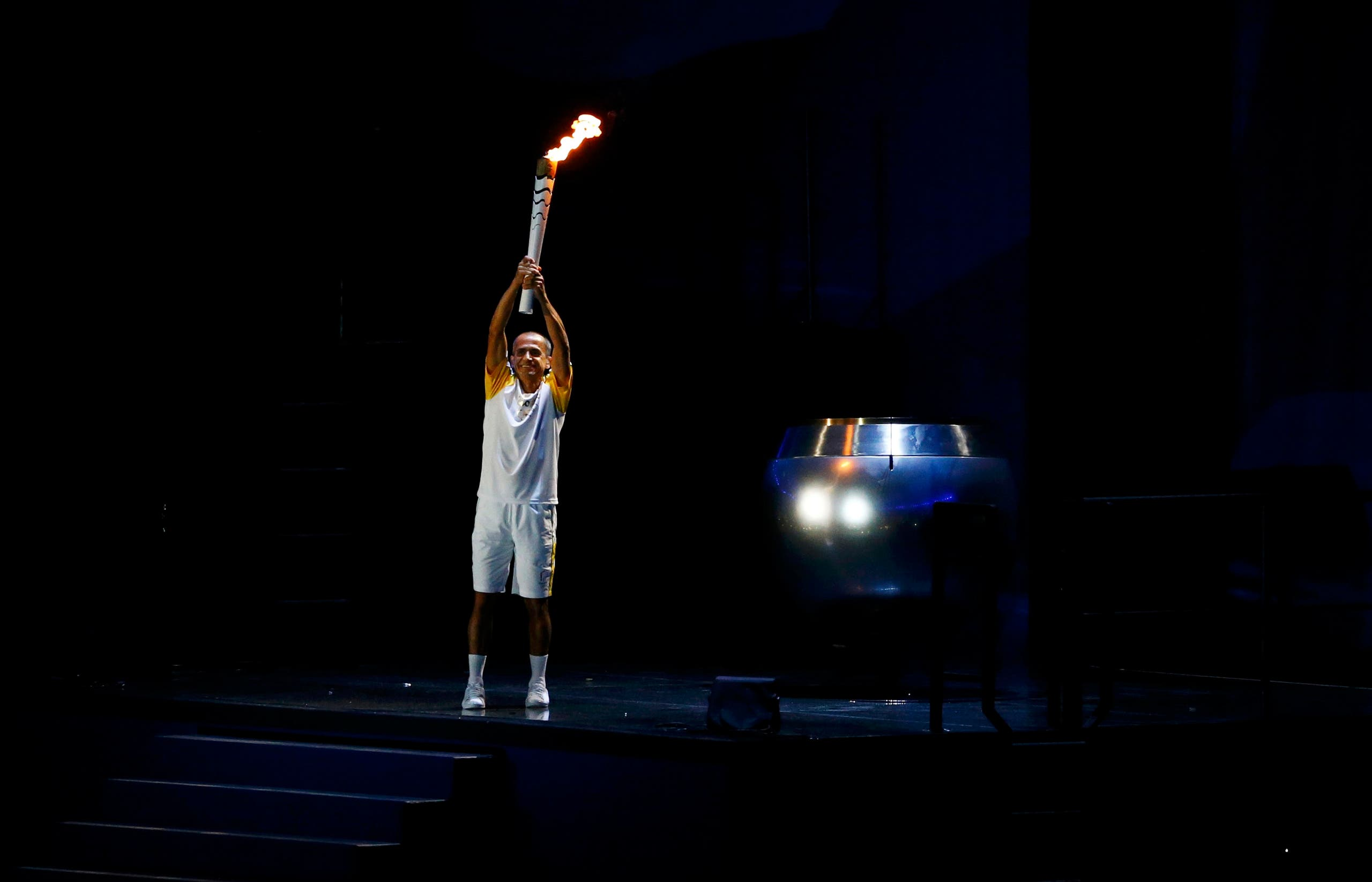 Former Brazilian marathon runner Vanderlei Cordeiro de Lima holds the Olympic torch before lighting the Olympic cauldron at the opening ceremony. REUTERS