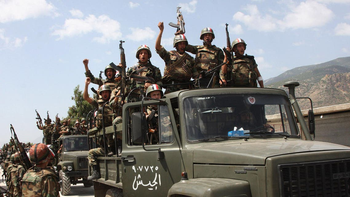 In this June 10, 2011, file photo, taken during a government-organised visit for media, Syrian army soldiers standing on their military trucks shout slogans in support of Syrian President Bashar Assad ap
