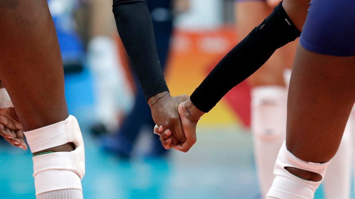 Italy's Paola Ogechi Egonu, left, and Myriam Fatime Sylla hold hands during a women's preliminary volleyball match against Serbia (Photo: AP)