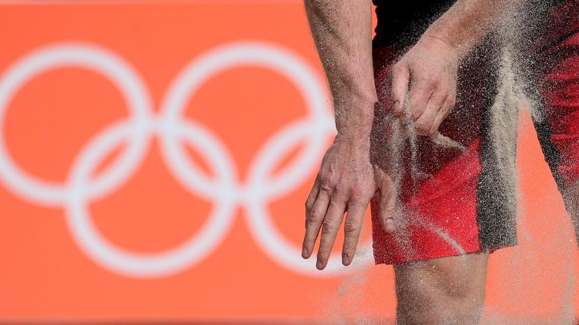 Canada's Joshua Binstock brushes his hands with sand during a men's beach volleyball match against Brazil (Photo: AP)