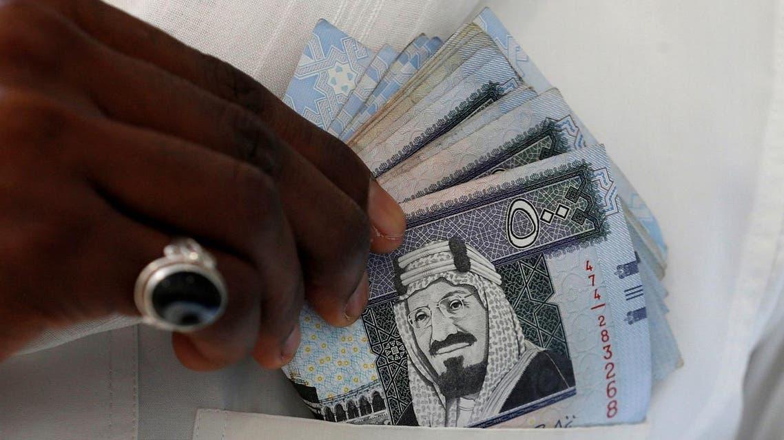 A Saudi man shows Saudi riyal banknotes at a money exchange shop, in Riyadh. (Reuters)