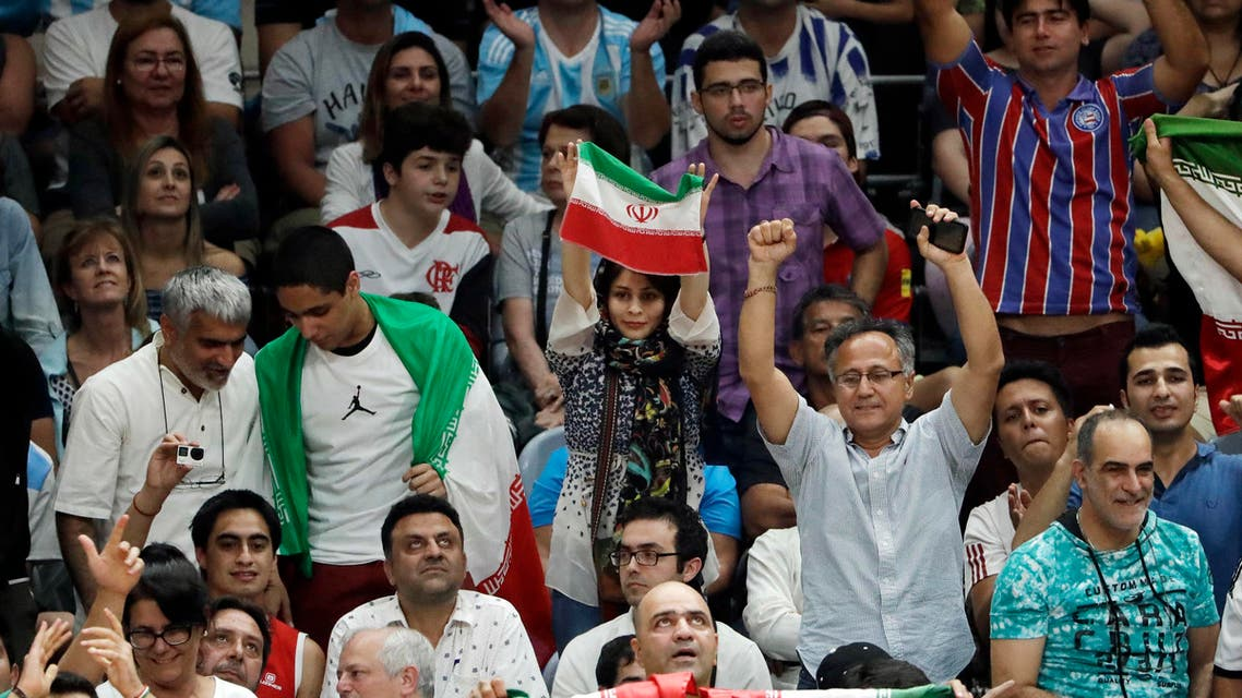 Holding a small Iranian flag Sajedeh Norouzi cheers on her country's team during a men's preliminary volleyball match between Iran and Argentina at the 2016 Summer Olympics in Rio de Janeiro, Brazil, Sunday, Aug. 7, 2016. AP
