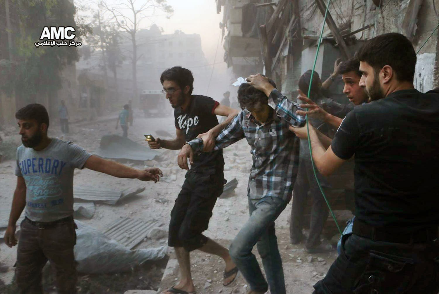 In this Sunday, July. 31, 2016 photo, provided by the Syrian anti-government activist group Aleppo Media Center (AMC), shows Syrians help an injured man, center, after airstrikes hit Aleppo, Syria (File Photo: Aleppo Media Center via AP)