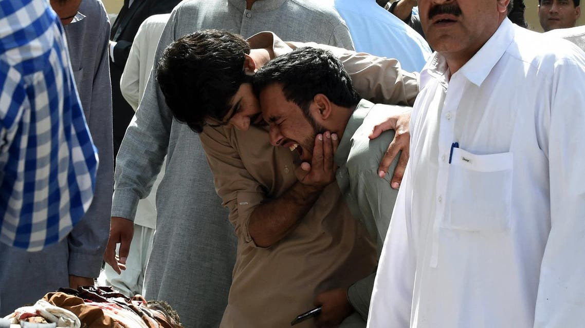 Pakistani local journalists react over the body of a news cameraman after a bomb explosion at a government hospital premises in Quetta. (AFP)