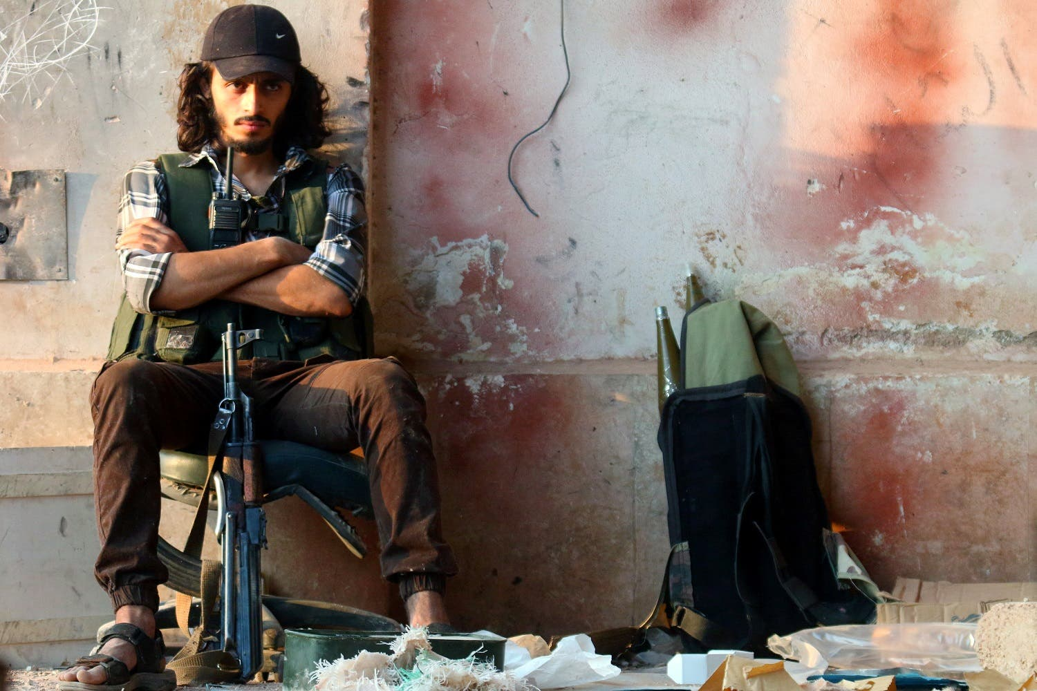 A rebel fighter sits with his weapon in the artillery academy of Aleppo. (Reuters)