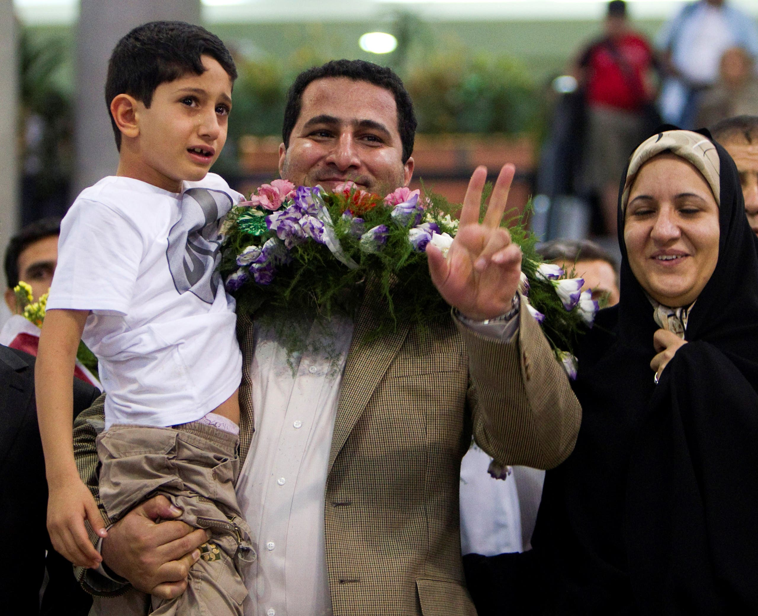 Iranian scientist Shahram Amiri flashes the victory sign as he arrives at the Imam Khomini Airport in Tehran, July 15, 2010. REUTERS