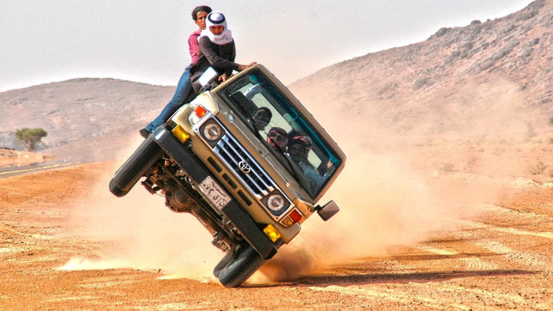 """Saudi youths demonstrate a stunt known as """"sidewall skiing"""" (driving on two wheels) in the northern city of Hail, in Saudi Arabia. (Reuters)"""