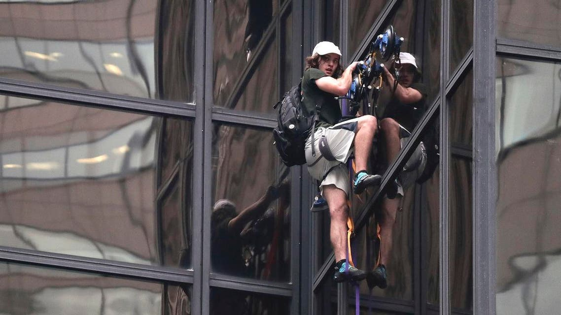 A man scales the all-glass facade of Trump Tower using suction cups Wednesday, Aug. 10, 2016, in New York