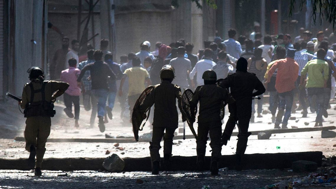 Indian policemen chase Kashmiri protesters in Srinagar, Indian-controlled Kashmir Friday, Aug. 12, 2016. AP