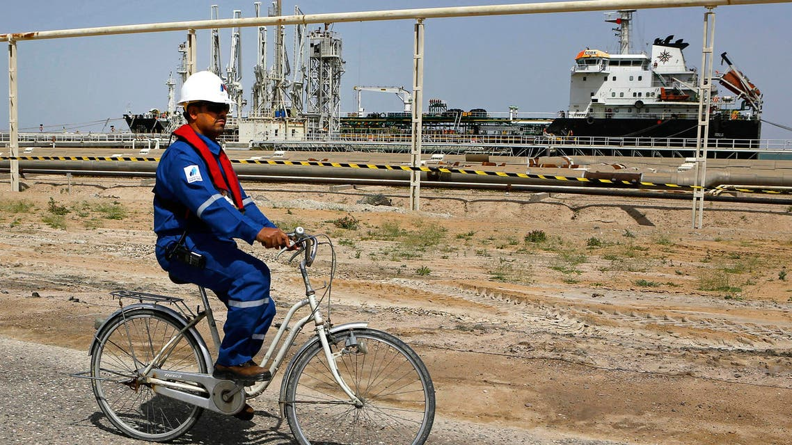 An Iraqi engineer rides a bicycle past a gas carrier as it prepares to set sail at the southern port of Umm Qasr, near Basra, Iraq, Sunday, March 20, 2016.