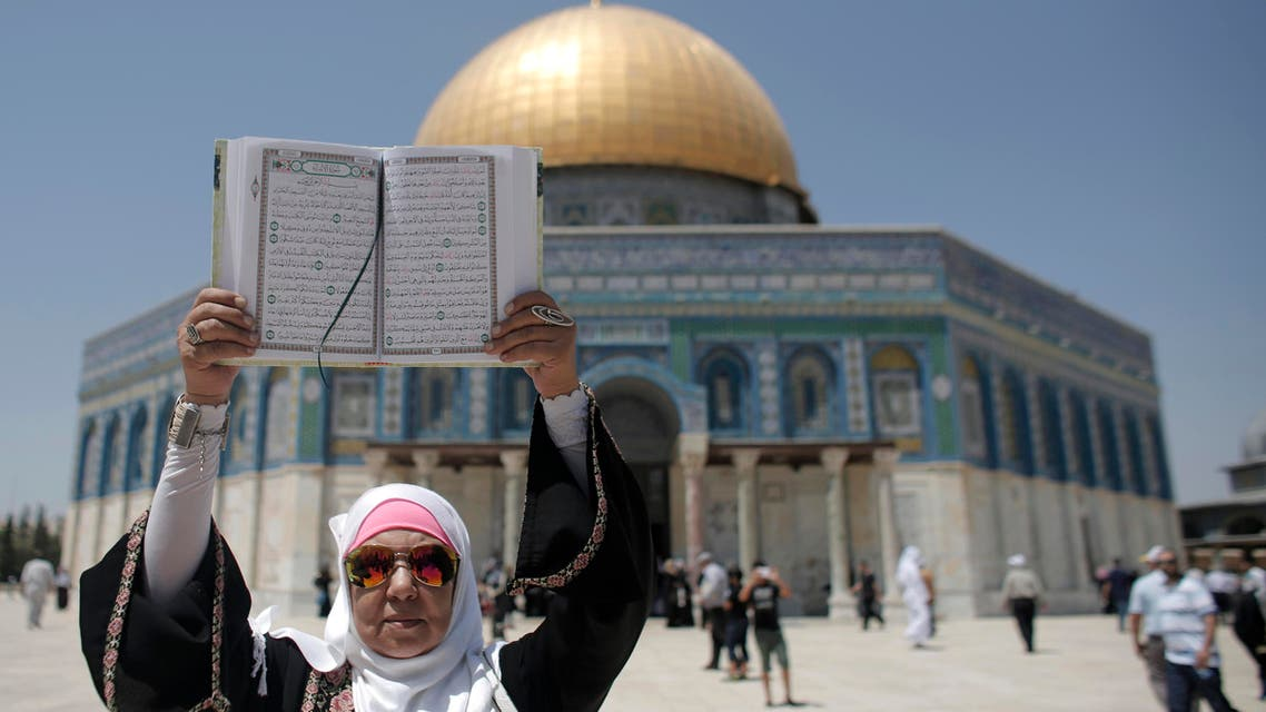 سيدة فلسطينية تحمل المصحف الشريف في المسجد الأقصى - فرانس برس
