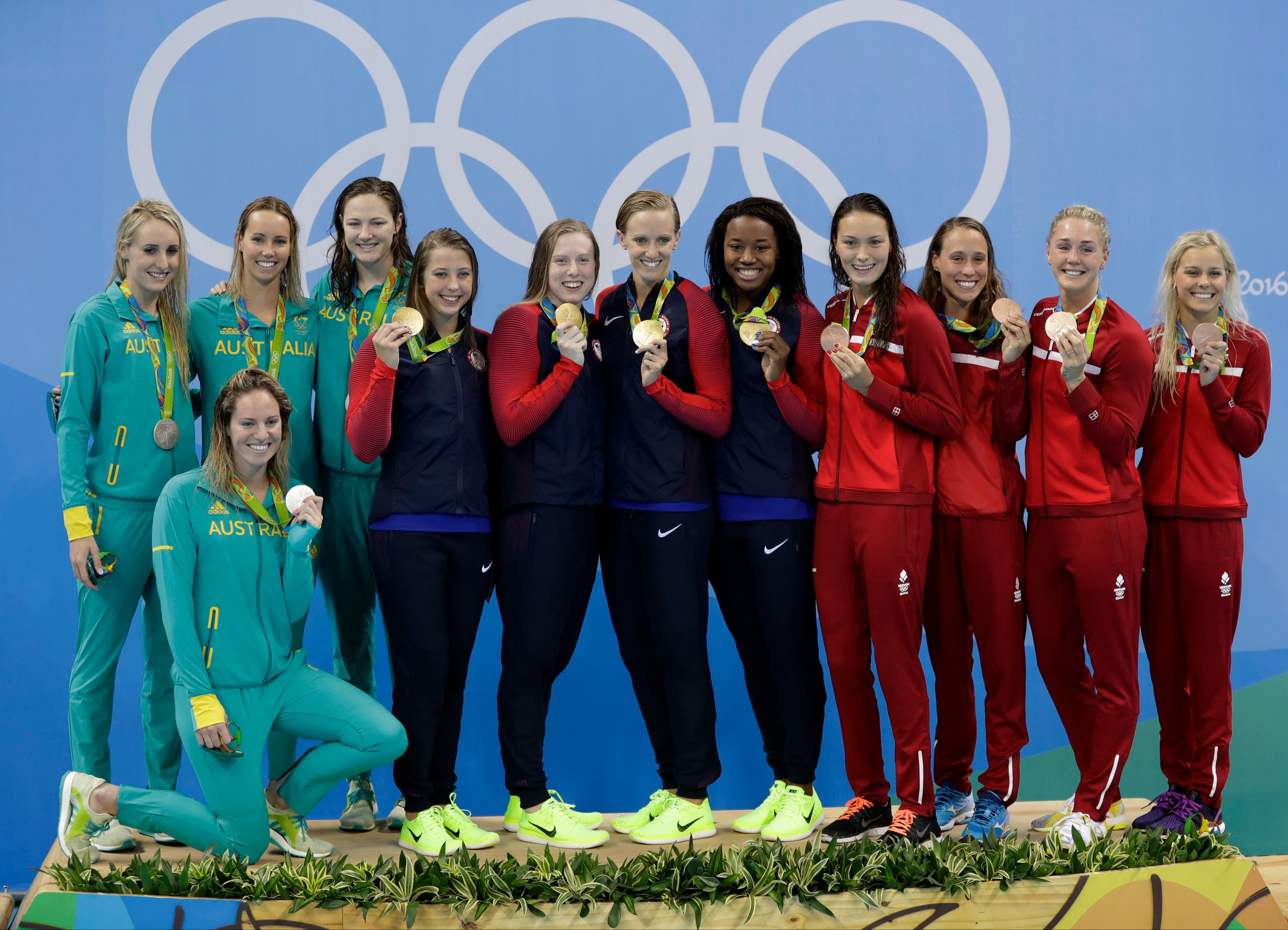 Team U.S., gold, center, and Denmark pose together on the podium after the women's 4 x100 meter medley relay during the swimming competitions at the 2016 Summer Olympics, Saturday, Aug. 13, 2016, in Rio de Janeiro, Brazil. (AP)