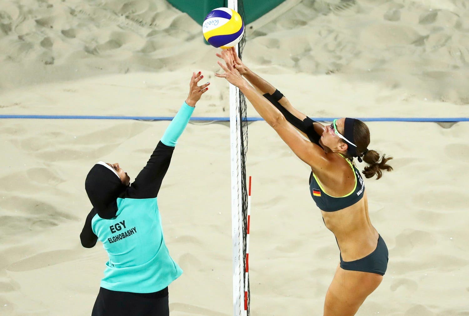 THE ICONIC HIJAB IMAGE: Doaa Elghobashy (EGY) of Egypt and Kira Walkenhorst (GER) of Germany compete in the Olympic beach volleyball. REUTERS/Lucy Nicholson