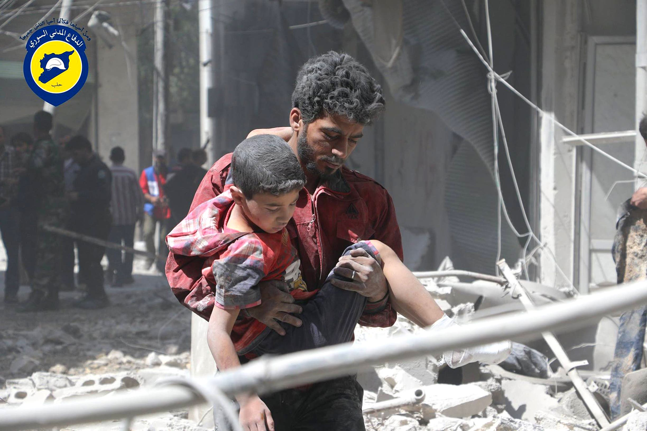 In this file photo taken on May 31, 2016 provided by the Syrian Civil Defense Directorate in Liberated Province of Aleppo, which has been authenticated based on its contents and other AP reporting, shows Syrian man carries an injured boy, in Aleppo, Syria. ap