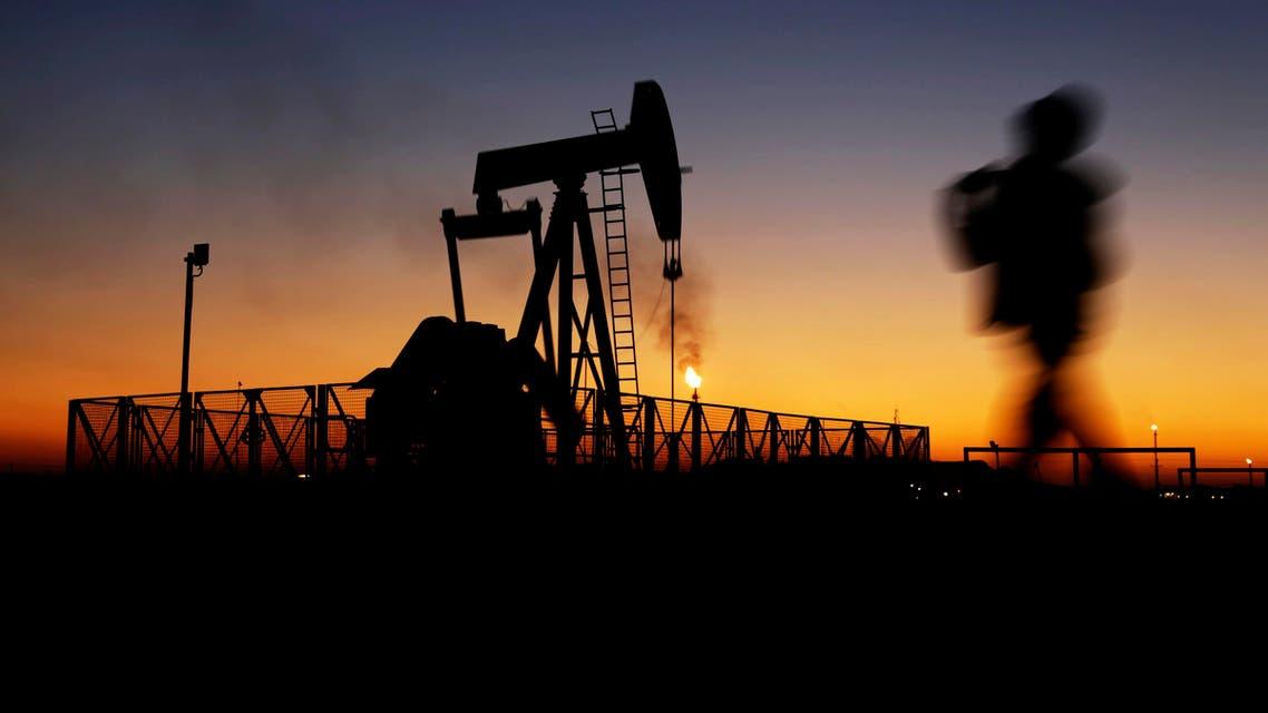A boy walks by an oil pump at sunset Monday, Jan. 18, 2016, in the desert oil fields of Sakhir, Bahrain. (AP)